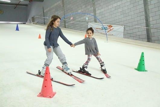 שתי ילדות מחזיקות ידיים וגולשות סקי בסקימולטור עמק חפר