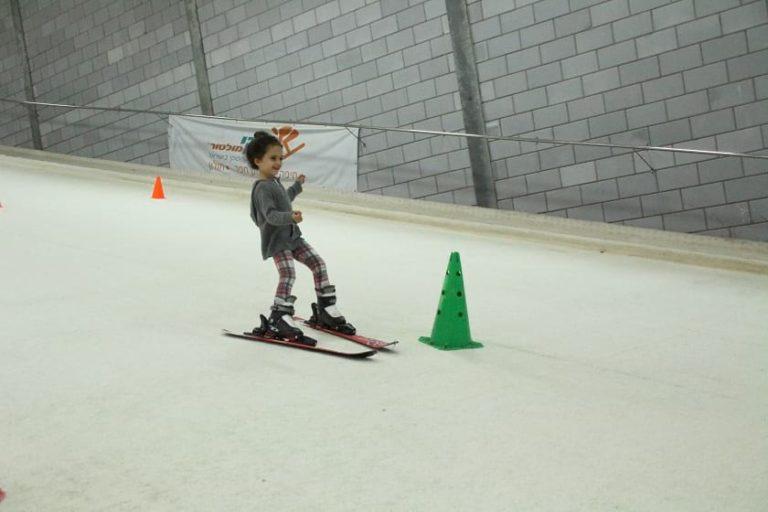 ילדה נהנית לגלוש סקי בסקימולטור